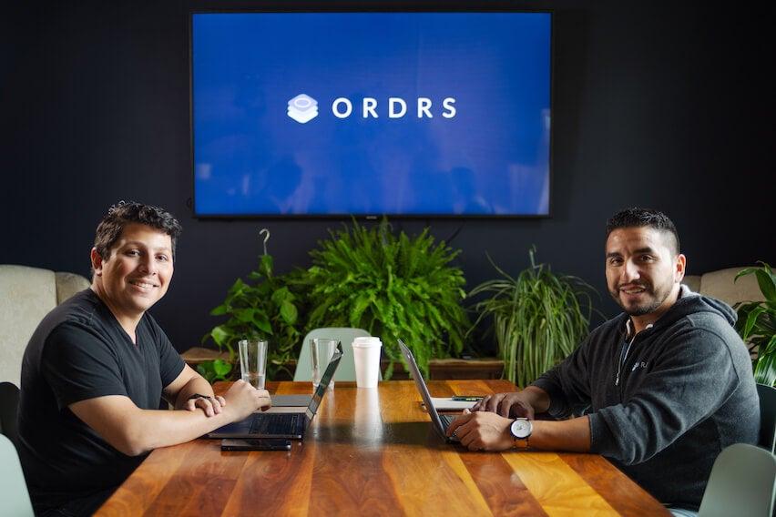Erik Ibarra and Steven Gonzalez Jr. sitting at desk in ORDRS office